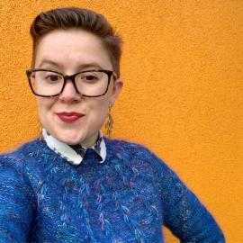 White woman with short red hair, glasses, and a blue sweater.